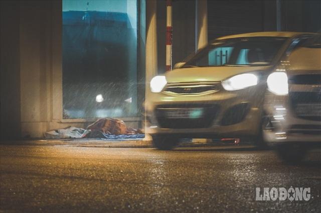 Hà Nội giá rét, người vô gia cư dùng áo mưa thay chăn để chống lạnh - 1
