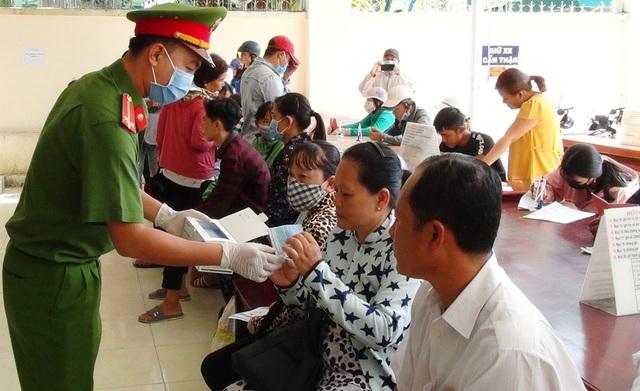 Công an Kiên Giang phát khẩu trang cho người dân đến làm thủ tục hành chính - 1