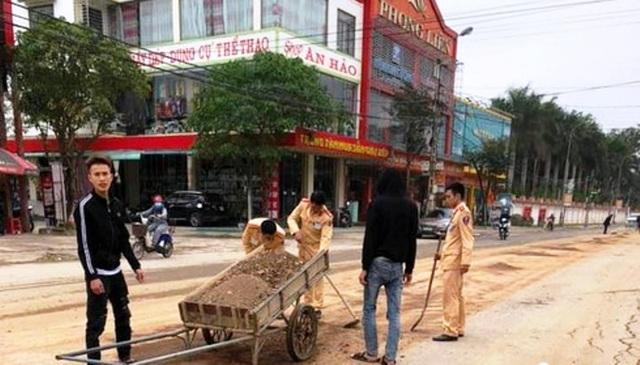 CSGT cùng người dân dọn đất, đá rơi vãi trên đường - 1