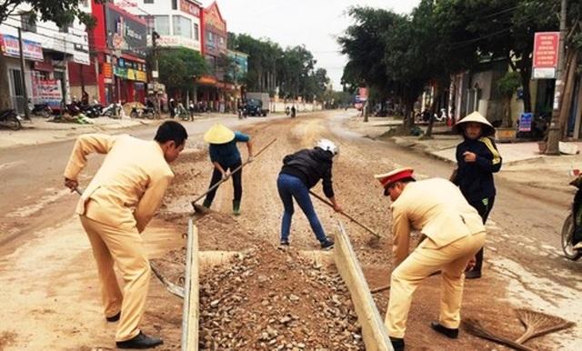CSGT cùng người dân dọn đất, đá rơi vãi trên đường - 2