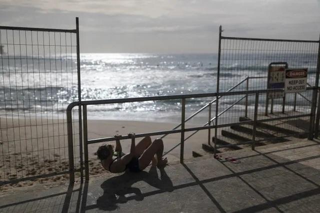 Bãi biển phong tỏa để chống dịch, du khách vẫn chui qua rào chắn đi bơi - 1