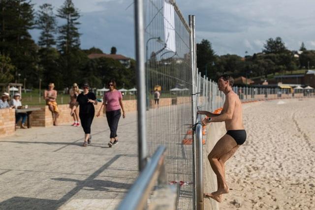 Bãi biển phong tỏa để chống dịch, du khách vẫn chui qua rào chắn đi bơi - 2
