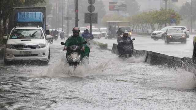TPHCM đón mưa giải nhiệt, người dân vất vả vượt rốn ngập - 1