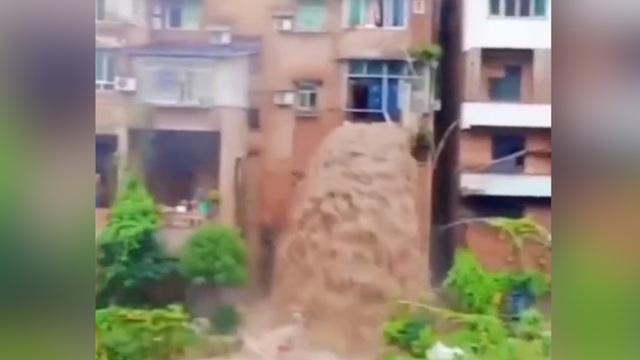Bùn lầy chảy từ cửa sổ nhà dân như thác nước tại Trung Quốc - 1