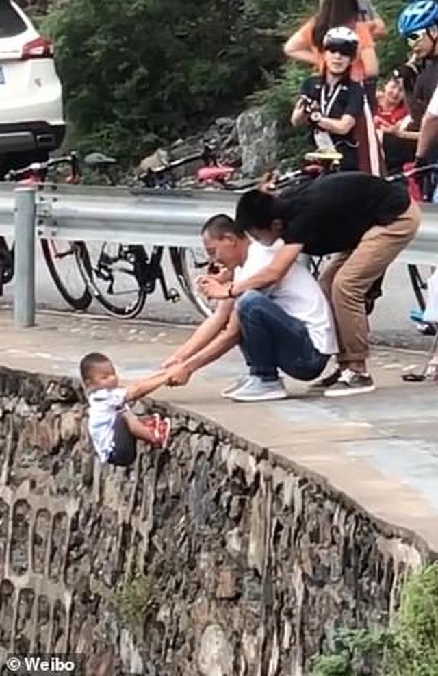 Cố chụp ảnh để đời, bố mạo hiểm để con trai nhỏ đu trên vách núi  - 1