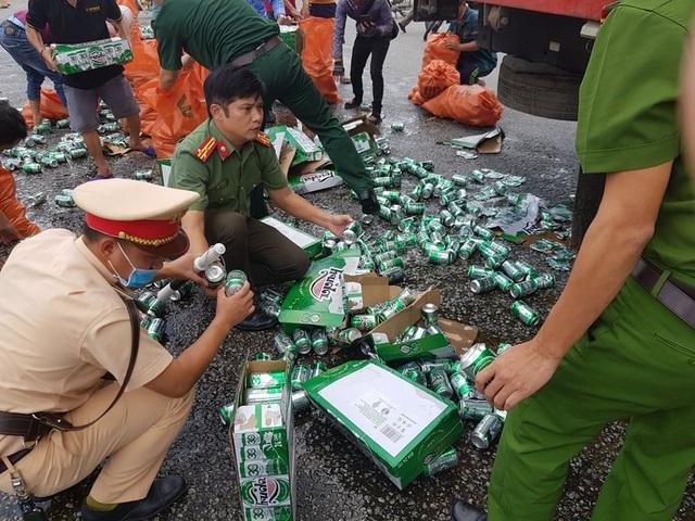 Người dân, công an giúp tài xế xe tải gom nhặt hàng trăm két bia bị rơi - 1