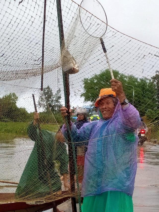 Người dân đổ ra đường giăng lưới bắt cá giữa lũ lớn - 8