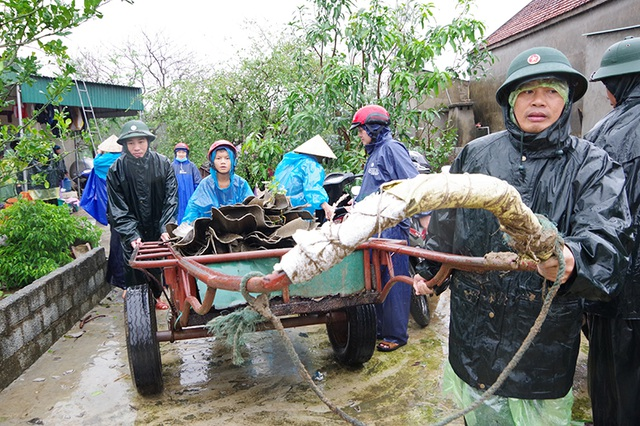Bộ đội dầm mình dưới cơn mưa xối xả giúp dân sửa nhà sau bão - 1