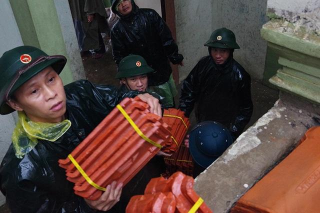 Bộ đội dầm mình dưới cơn mưa xối xả giúp dân sửa nhà sau bão - 3