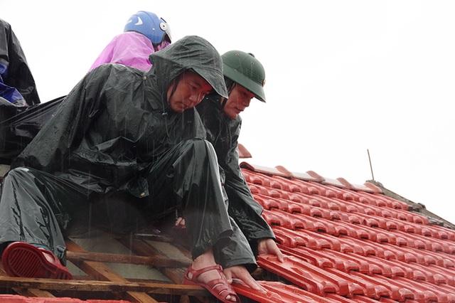 Bộ đội dầm mình dưới cơn mưa xối xả giúp dân sửa nhà sau bão - 5