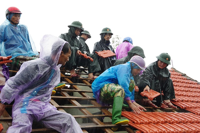 Bộ đội dầm mình dưới cơn mưa xối xả giúp dân sửa nhà sau bão - 4