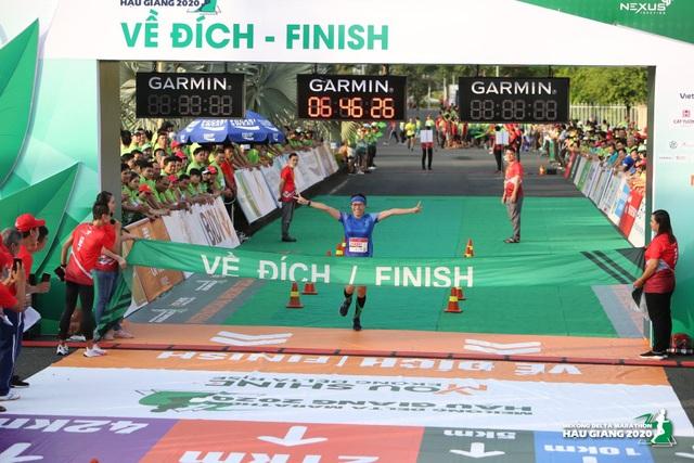 Các VĐV chúc mừng ông Đoàn Ngọc Hải về đích tại giải marathon Hậu Giang - 1