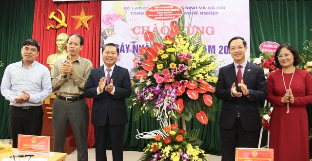 Thứ trưởng Bộ Lao động - Thương binh & Xã hội Lê Tấn Dũng (giữa) tặng hoa, chúc mừng các cán bộ, nhà giáo giáo dục nghề nghiệp.