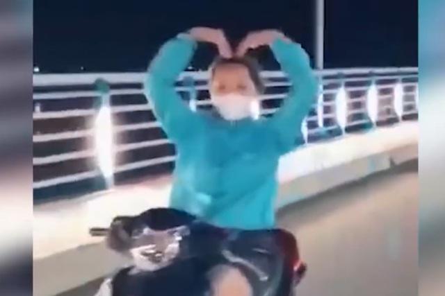 Cô gái trẻ buông tay lái xe máy để… múa quạt! - 2