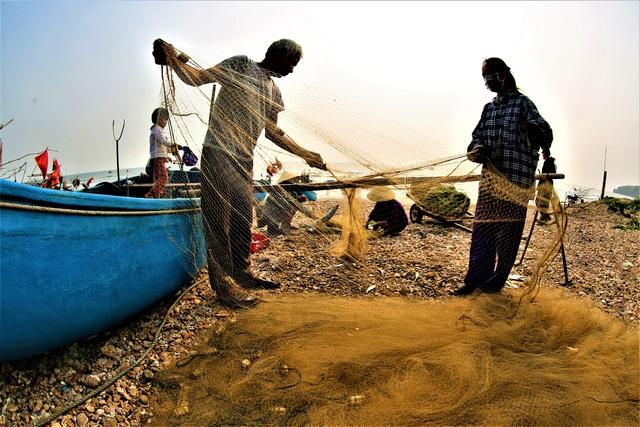 Sau khi thu hoạch các loại hải sản dính lưới, các ngư dân làm sạch lưới chuẩn bị cho một chuyến đi mới.