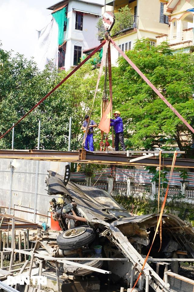 Cảnh cần cẩu nhấc bổng xác pháo đài bay B-52 dưới đáy hồ lên bờ ở Hà Nội - 6