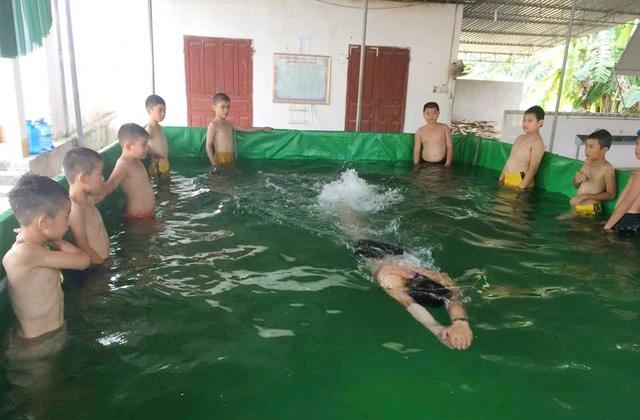 Các học sinh Trường Tiểu học thị trấn Anh Sơn học bơi trong chiếc bể mini của thầy Thanh dưới sự hướng dẫn của giáo viên thể dục.