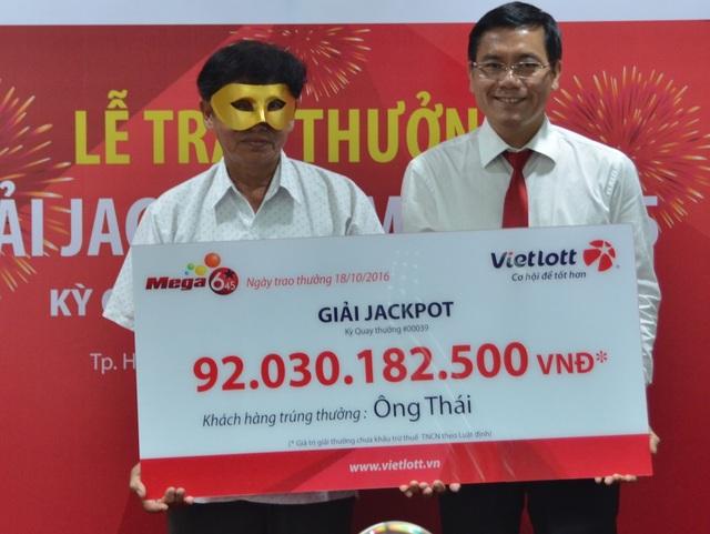 Ông Thái (phải) đeo mặt nạ lúc nhận thưởng để tránh những rắc rối sau một đêm trở thành tỉ phú?