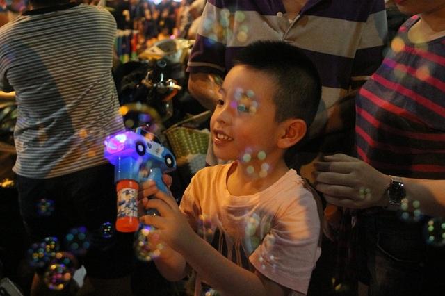 Một em nhỏ hào hứng chơi trò bắn súng bóng trong không gian đi bộ ở phố Hàng Mã
