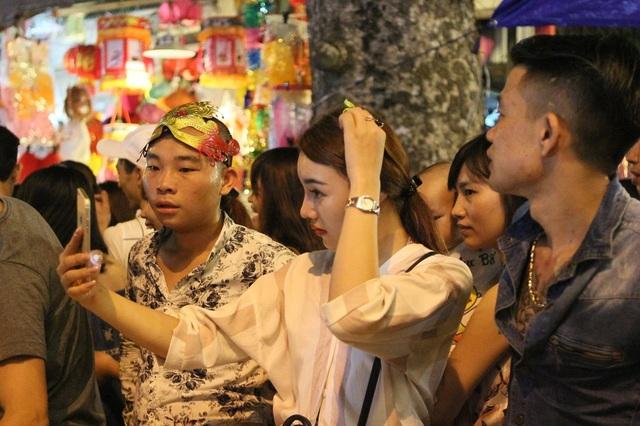Năm nay thời tiết Hà Nội được xem là mát mẻ và thuận lợi để người dân vui đón Tết Trung thu. Trên phố Hàng Mã, nhiều bạn trẻ tranh thủ ghi lại những khoảnh khắc đáng nhớ trong đêm hội trăng rằm.