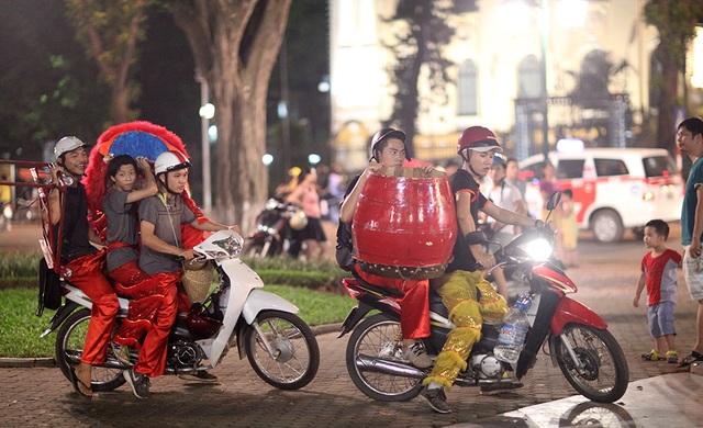 Một nhóm múa lân vừa kết thúc phần biểu diễn tại vườn hoa Lý Thái Tổ đã vội vàng di chuyển đến địa điểm khác. Một số thành viên trong đoàn không đội mũ bảo hiểm và vận chuyển các đạo cụ khá cồng kềnh.