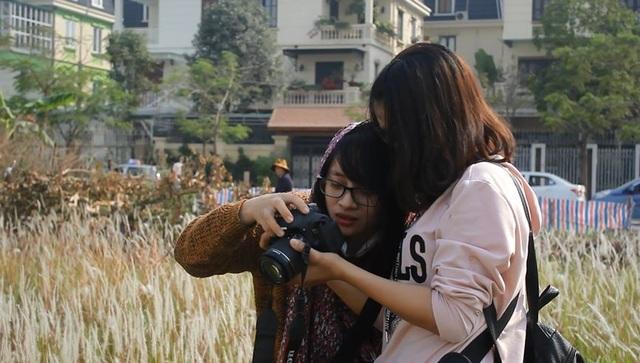 Đôi bạn trẻ tranh thủ xem lại những bức ảnh vừa chụp được.