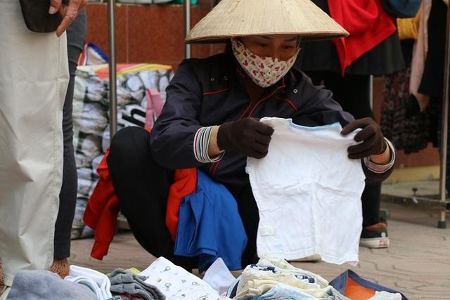 Một người lao động nghèo đang cẩn thận lựa chọn những chiếc áo ấm cho con trai của mình.