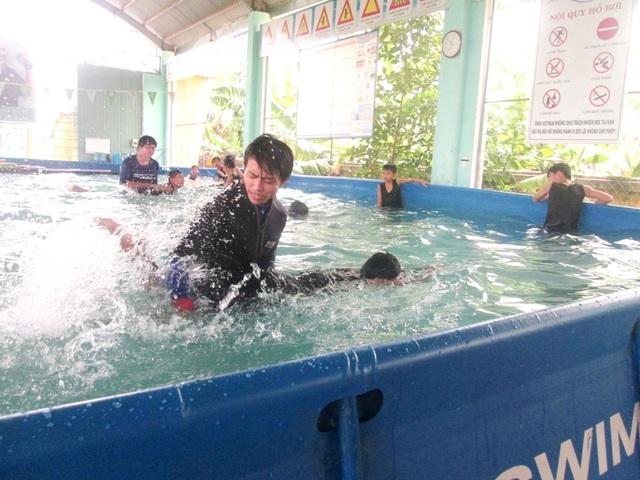 Thầy dạy bơi đang hướng dẫn các em học sinh tập bơi trong bể bơi ở trường tiểu học Nguyễn Đức Thiệu