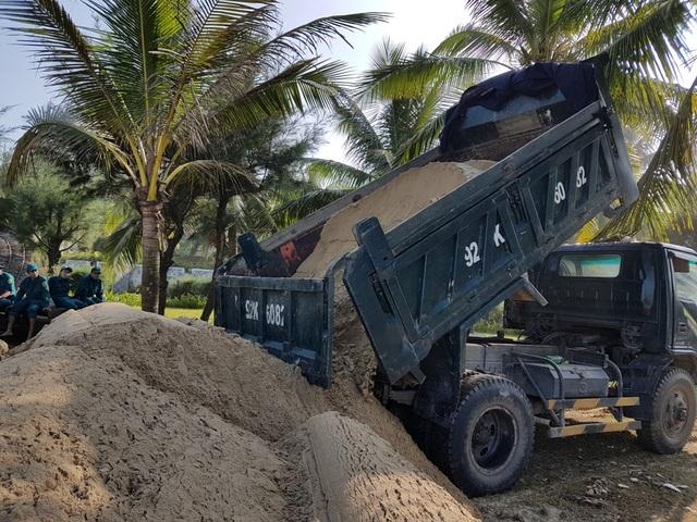Xe tải cát được chở đến để cho vào bao, gia cố bờ biển.