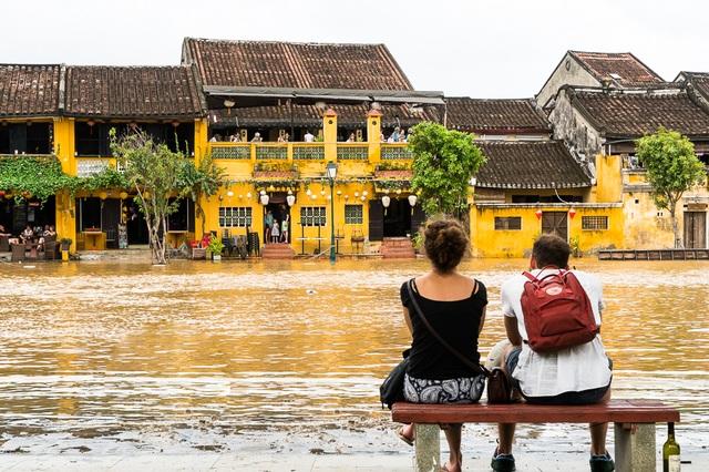 Hai du khách nước ngoài ngồi bên bờ An Hội ngắm phố cổ Hội An mênh mông nước