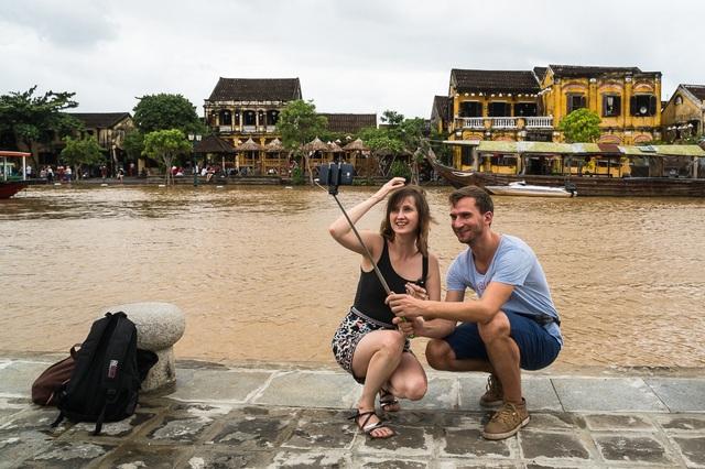 Hai du khách nước ngoài tự sướng với dòng sông Hoài mùa lũ