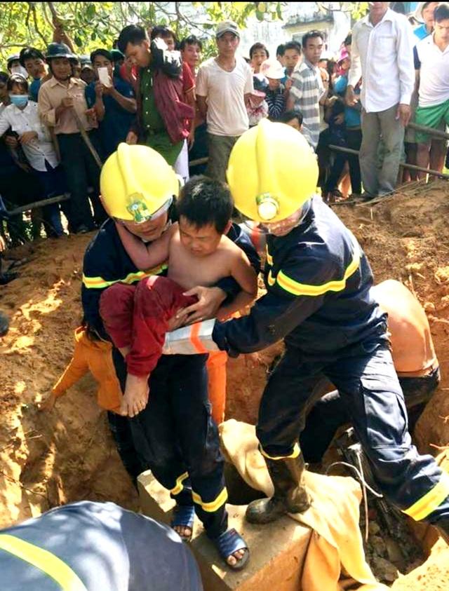 Cháu Quang được cứu khỏi hố móng trụ điện trong sự vui mừng của người dân. (Ảnh: Cảnh sát PCCC Quảng Nam)