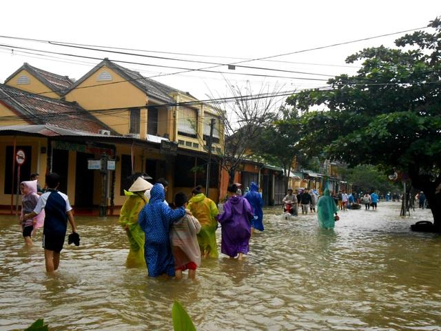 Nước lũ dâng cao và chảy xiết gây ảnh hưởng, nguy hiểm đến việc đi lại của người dân Hội An