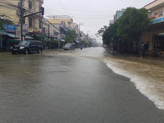 Nước lũ bắt đầu tràn qua con đường chính ở trung tâm thị xã Điện Bàn