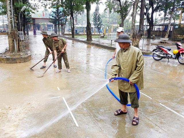 Lực lượng Công an xã Đại An giúp trường dọn bùn non trong sân trường