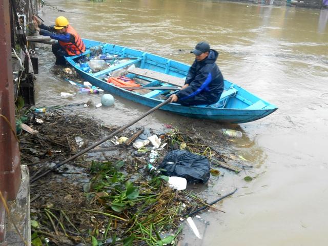 Công nhân phải rất vất vả để dọn lượng rác khổng lồ do lũ đem tới