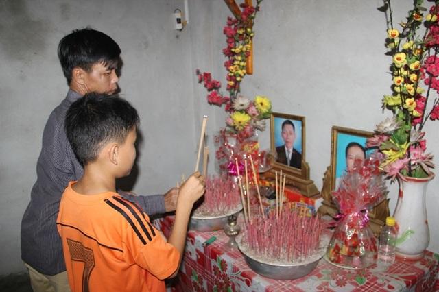 Hai chú cháu thắp hương lên bàn thờ của cha mẹ cháu Chiến