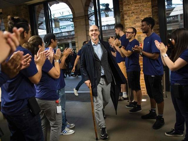 Nhân viên cửa hàng Apple store ở Anh đứng xếp thành hai hàng và vỗ tay chào đón những vị khách đầu tiên đến mua hàng tại khu phố Covent Garden, London