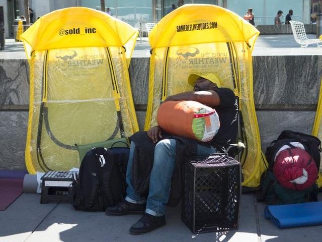 Một người đàn ông ngủ gục khi đang xếp hàng trước Apple store tại phố Fifth Avenue, New York vài giờ trước khi ra mắt iPhone 7