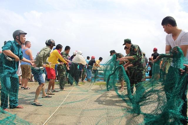 Các chiến sĩ giúp dân kéo lưới lên bờ giải cứu tàu cá mắc cạn