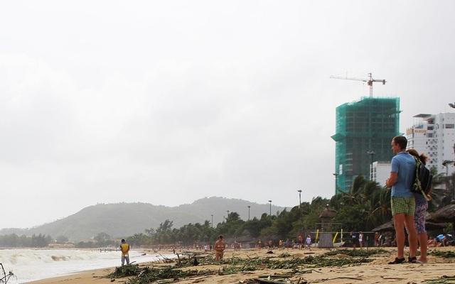 Du khách thư giãn trên bãi biển mùa sóng lớn