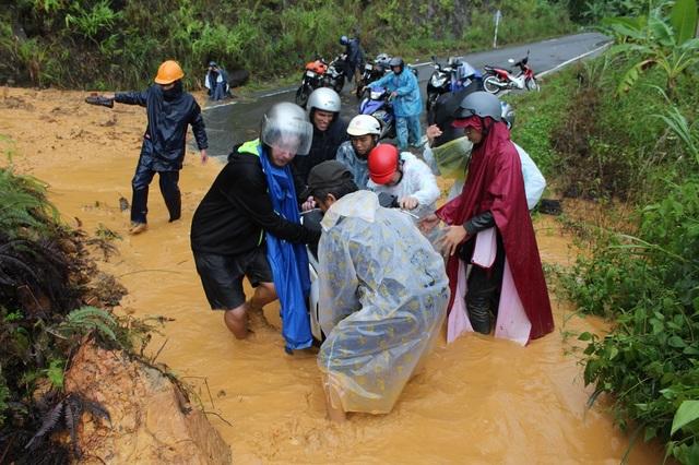 Người đi đường giúp nhau khiêng xe máy qua một điểm sạt lở trên tuyến đèo Khánh Lê (Khánh Vĩnh, Khánh Hòa)