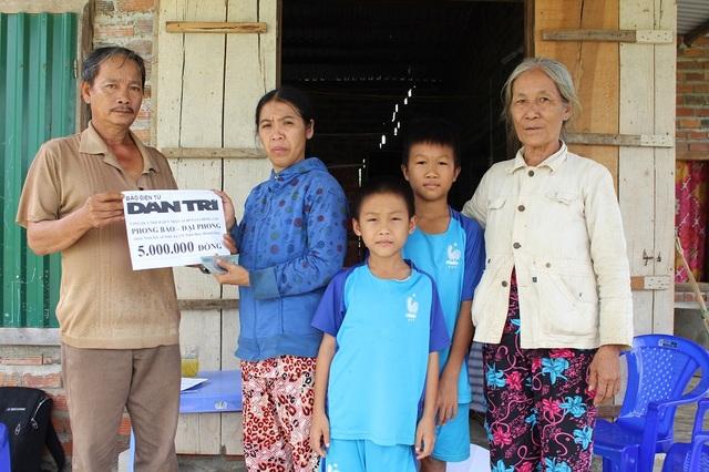 Đại diện chính quyền địa phương cùng PV Dân trí trao đến gia đình 2 cháu bé số tiền 5 triệu đồng do Quỹ Nhân ái - Báo Dân trí hỗ trợ