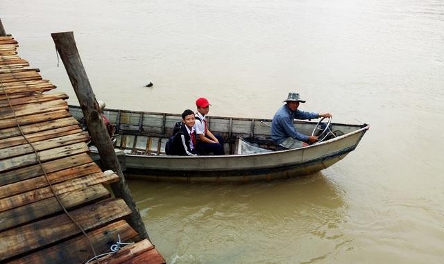 Thuyền của ông Khanh chui qua cầu gỗ Phú Kiểng trước khi cập bờ ở phía Nam chân cầu