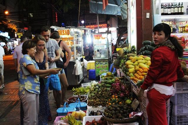 Du khách Nga bên một gian hàng trái cây ở phố Tây Nha Trang