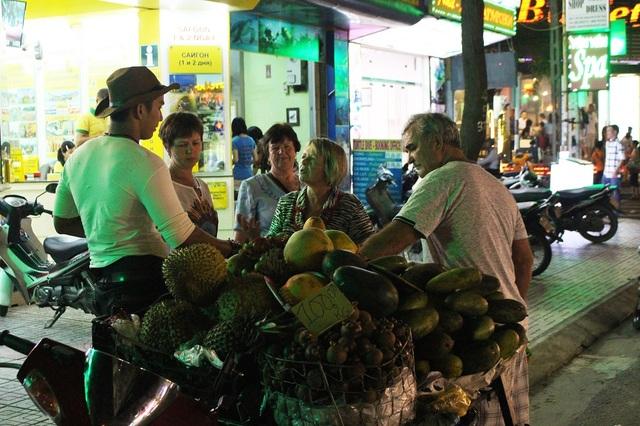 Du khách Nga tản bộ và dừng chân bên một gian hàng trái cây di động của một anh chàng cao bồi Việt Nam