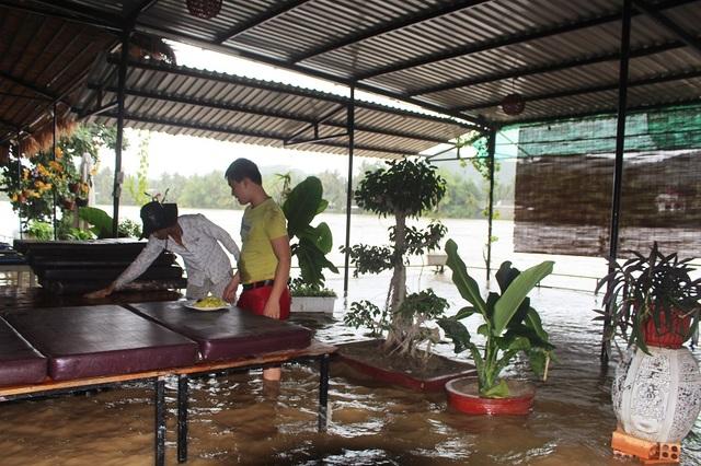 Mặt nước sông Cái ở TP Nha Trang tràn vào một nhà hàng ven sông và các nhân viên nháo nhào thu dọn đồ đạc