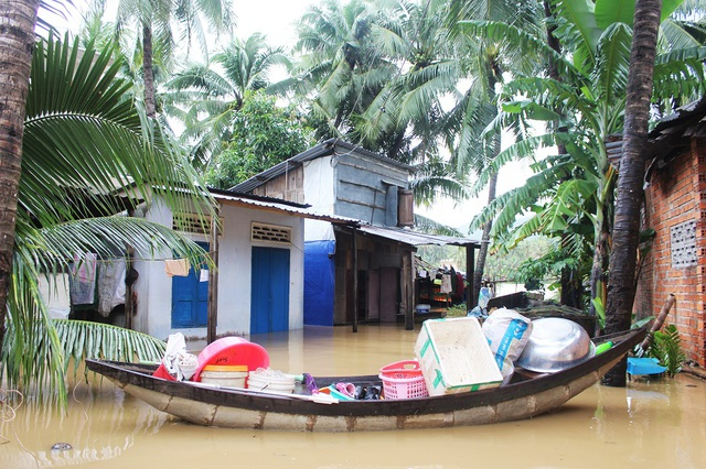 Nhà dân ở phường Ngọc Hiệp (TP Nha Trang) bị ngập sâu và phải chất đồ lên một con thuyền để chạy lũ