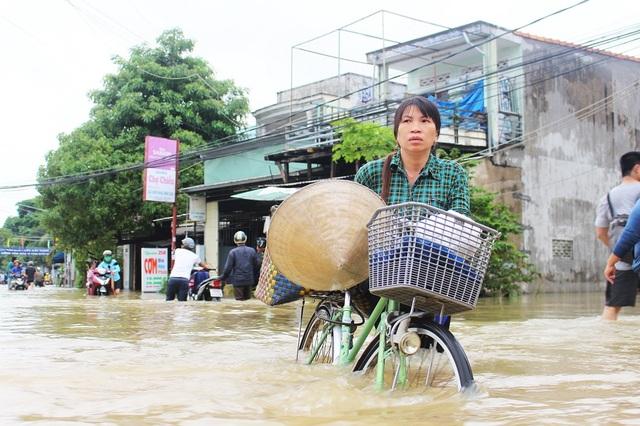 Một phụ nữ với vẻ mặt hốt hoảng khi vượt qua đoạn đường bị ngập lụt