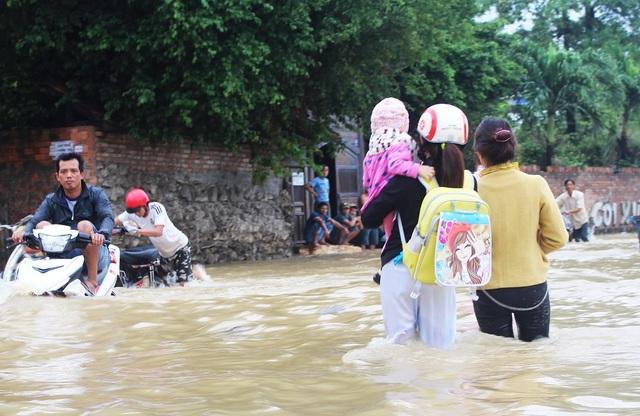 Một phụ nữ Nha Trang bế con vượt lũ về nhà